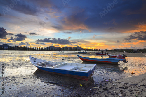Wallpaper Mural Fisherman boat on mud during lowtide with dramatic sunset at background