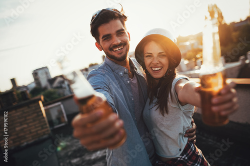 Fotografering Young happy couple toasting with beer outdoors