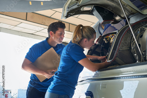 Aero Engineer And Apprentice Working On Helicopter In Hangar