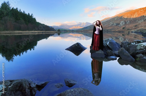 Canvas Print Woman with long red hair reflected in still lake