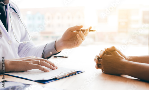 Fotografia Doctor hand holding pen and talking to the patient about medication and treatment
