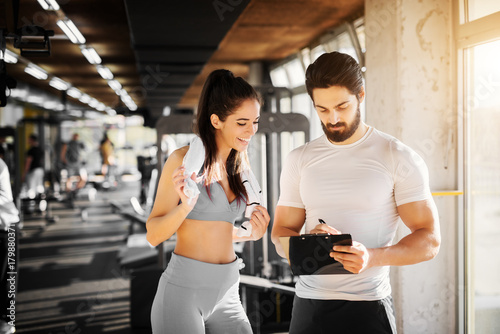 Young slim fitness girl standing with a towel near handsome trainer while showing her schedule for next week in the gym Fototapet