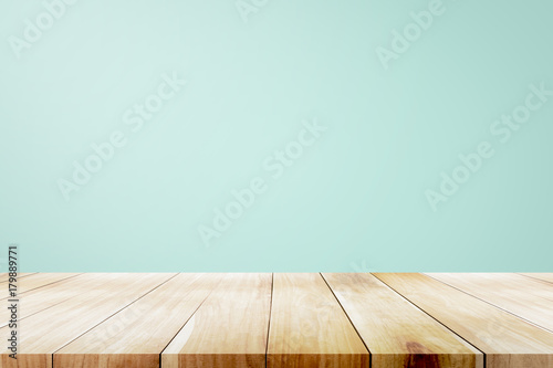 Fotografia Empty wooden deck table over mint wallpaper background.
