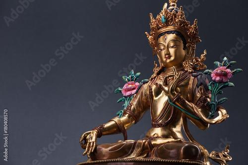 Bronze figurine of a green Tara with copyspace.
