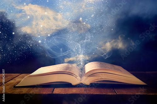 obraz otwartej antycznej książki na drewnianym stole z nakładką brokatu.