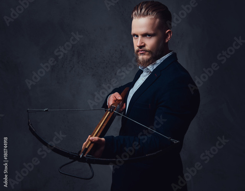 Stampa su Tela A man dressed in a suit holds crossbow.