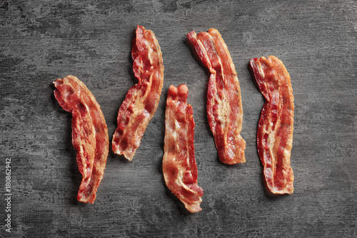 Cooked bacon rashers on wooden table