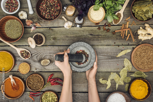 Fotografia woman grinding pepper with pestle and mortar
