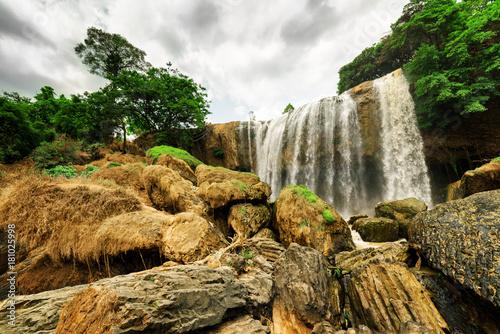 Fototapeta Wodospad wśród kamieni i drzew na ścianę