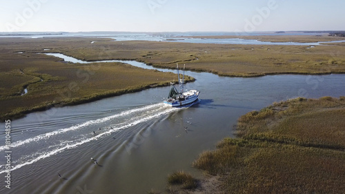 Aerial view of commercial fishing boat coming into port.