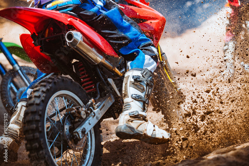 Photo Close-up part of mountain bikes race in dirt track with flying debris during an acceleration in sunshine day time