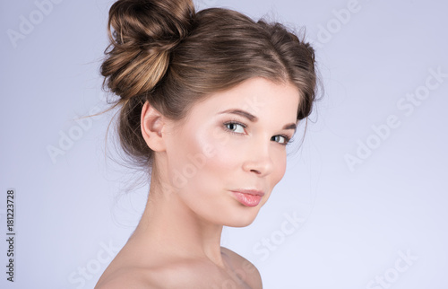Vertical portrait of cute woman model with fresh daily makeup and cute wavy hairstyle. Fashion shiny highlighter on skin. Sexy look