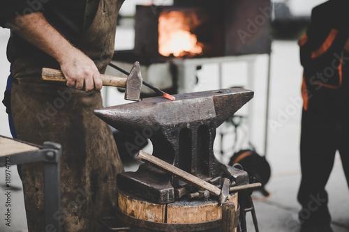 Obraz na płótnie The blacksmith manually forging the molten metal on the anvil in smithy with spa