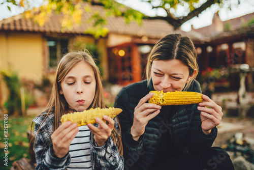 Girls eating sweet corn outdoor