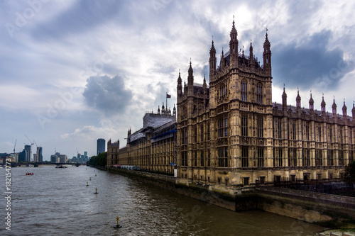 Fototapeta Palace of Westminster, Dramatic Shot over River Thames in front of Moody Clouds