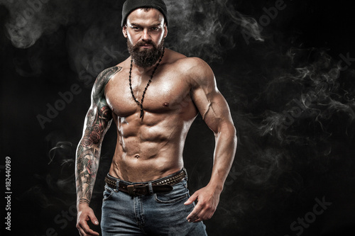 Photo Handsome fit man posing wearing in jeans with tattoo