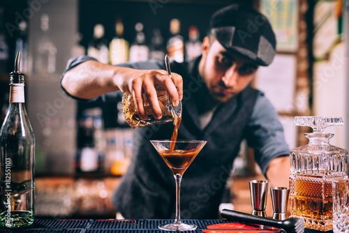 Barman creating signature drink at bar counter. Bitter whisey with beer cocktail