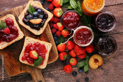 Sandwiches with plum, strawberry jam and fresh fruits on wooden background