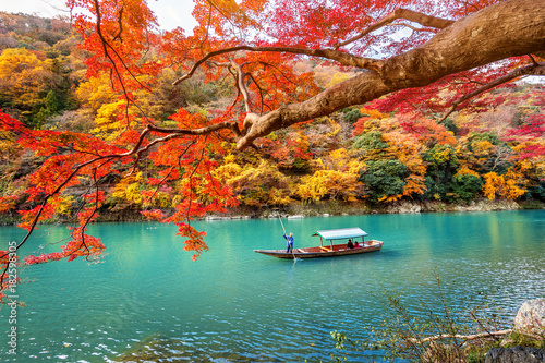 Fototapeta premium Boatman punting łódź na rzece. Arashiyama w sezonie jesiennym wzdłuż rzeki w Kyoto, Japonia.