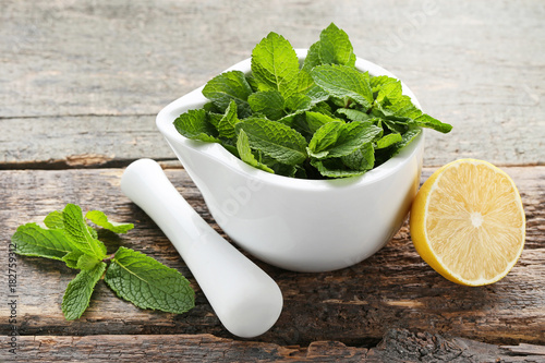 Fresh mint leafs in mortar with lemon on grey wooden table