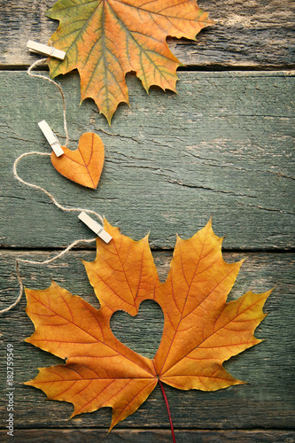 Dry maple leafs with heart on grey wooden table