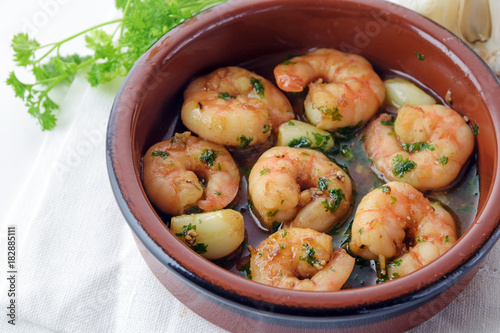 prawns or shrimps with garlic and parsley in sherry sauce in a tapas bowl, spanish appetizer gambas al ajillo, white tablecloth