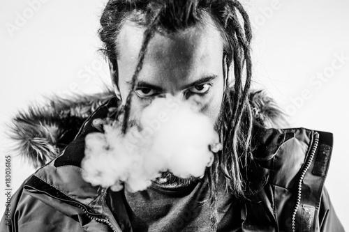 Man dreadlocks smoking electronic cigarette.