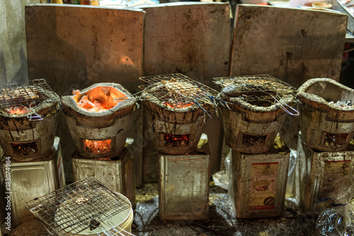 Barbecue in the streets of Bangkok, the best place for street food in the world. Gridiron with fish and lobster over charcoal grill