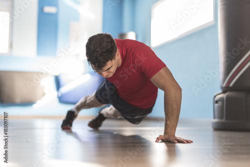 Jove hombre entrena flexiones a una mano en el suelo del gimnasio Fotobehang