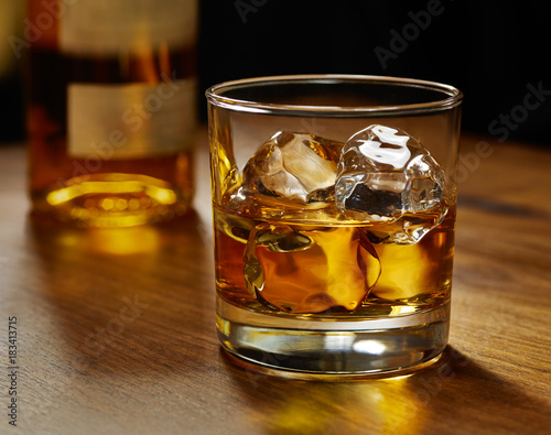 Canvas Print Glass of whiskey on ice with bottle on wood bar