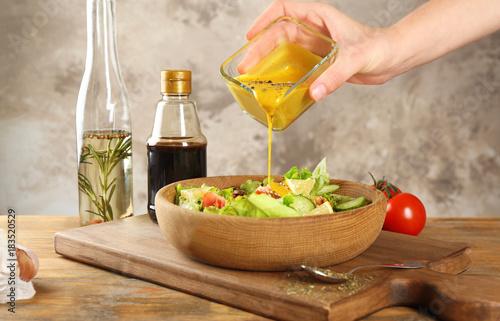 Obraz na płótnie Woman pouring honey mustard dressing into bowl with fresh salad on table