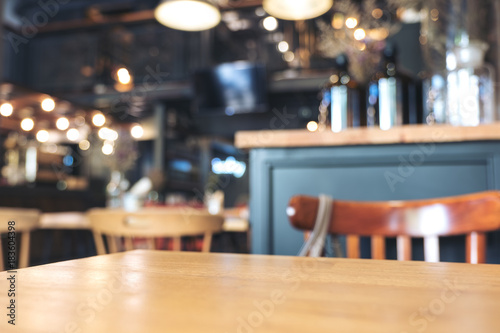 Foto Wooden table and chairs in modern loft cafe with blur bokeh vintage background