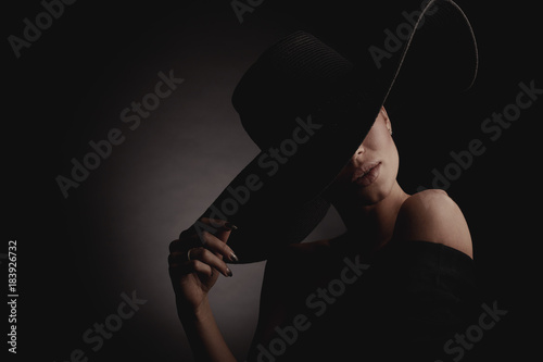 Dramatic dark studio portrait of elegant woman in black wide hat and black dr...