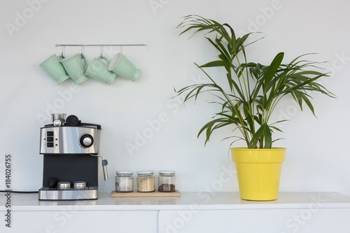 Leinwand Poster Coffeemaker, pot plant and mugs hanging on hook