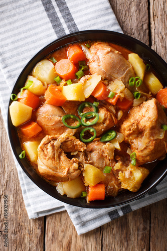 Spicy stewed chicken with vegetables close-up in a bowl. Vertical top view