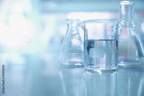 experiment water in beaker and flask in chemistry science laboratory background