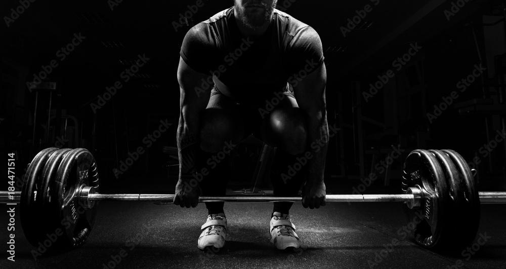 Ogromny człowiek przygotowuje się do wykonania ćwiczenia zwanego martwym ciągiem. <span>plik: #184471514 | autor: andy_gin</span>