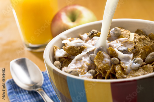 Canvas Print Milk pouring over a bowl of cereal with a spoon, apple and orange juice in the background
