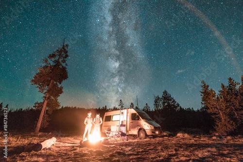 Vanlife couple standing in front of campfire and van under Milky Way night sky Fototapet