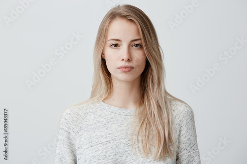 Fotografia Confident good-looking beautiful woman with blonde dyed hair with healthy pure skin dressed in casual clothes looking seriously at camera