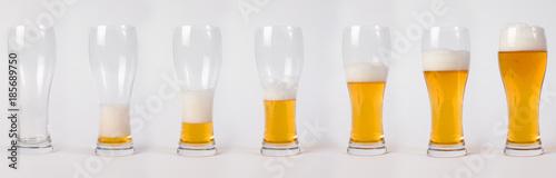 Fotografia Lager beer in glass. Steps of filling glass of beer.