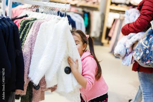 Adorable little girl choosing clothes Fototapeta
