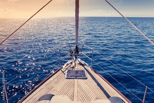 Carta da parati Ship's Bow, sailing yacht deck with open sea and warm sunlight