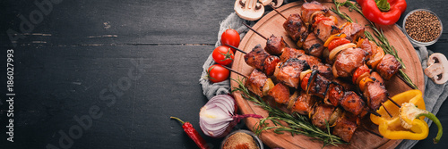 Shish kebab on skewers with onions. On the black wooden table. Fotobehang