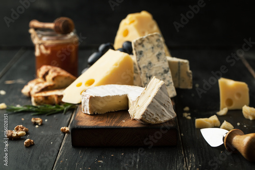 Assorted cheeses with grapes, nuts and rosemary