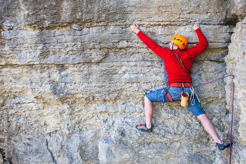 Canvas-taulu Climber in a helmet climbs up.
