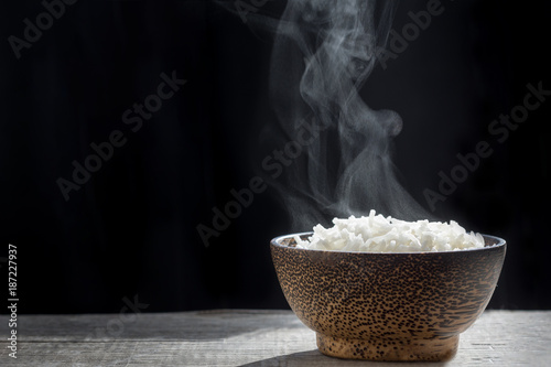 Fotografie, Obraz Cooked rice with steam in wooden bowl on dark background,hot cooked rice in bowl