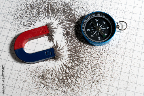 Photo Red and blue horseshoe magnet or physics magnetic and compass with iron powder magnetic field on white paper graph background