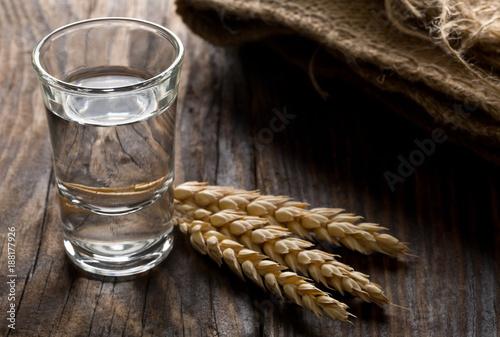 Photo German hard liquor Korn Schnapps in shot glass with wheat ears