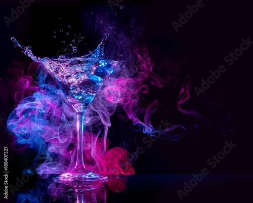 cocktail splashing and multicolored smoke in a black background